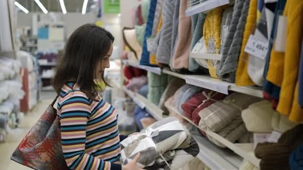 Femme Choisir Plaid doux en magasin pour la maison