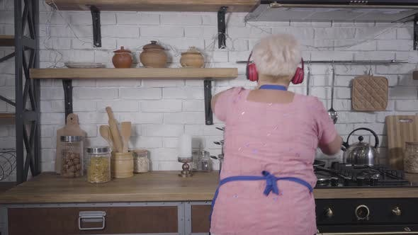 Thumbnail for Back View Close-up of Positive Senior Caucasian Woman Dancing While Cooking at the Kitchen