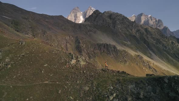 Aerial Shot of a Man Climbing Mountains on a Sunny Day in Autumn