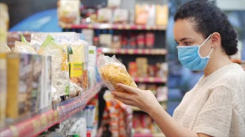 Young Woman in a Mask From a Coronavirus Epidemic Is Standing in the Grocery Department of a