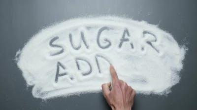 Sugar addict. Hand writes words sugar addict on sugar background.