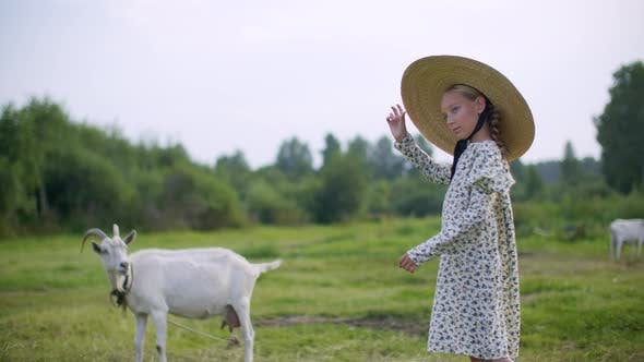 Thumbnail for Rural Girl in Hat and Romantic Dress Posing with Goat on Countryside Field. Country Girl Walking on