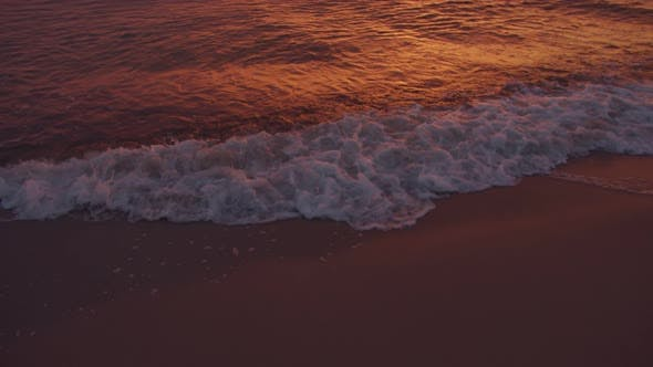 Sea waves on the beach at sunset background