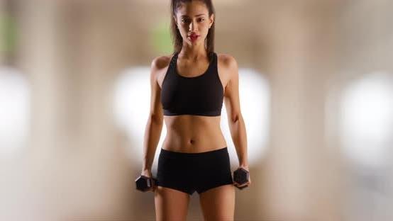 Ein Latina Mädchen ist dabei, Gewichte im Fitnessstudio zu heben