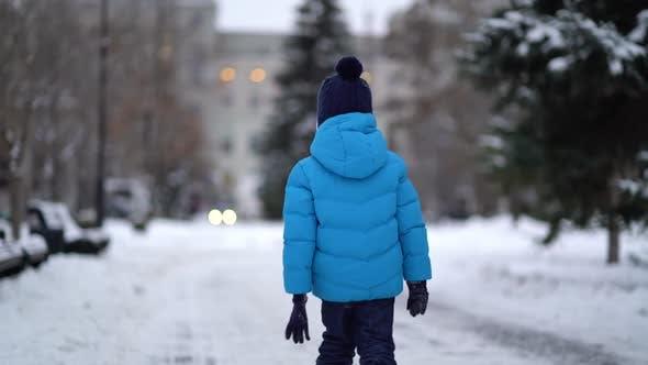 Thumbnail for Niedlich vier Jahre alt Junge in blau Winter Kleidung Spaziergänge in verschneite Straße