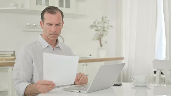 Focused Middle Aged Man Working on Laptop and Document at Home