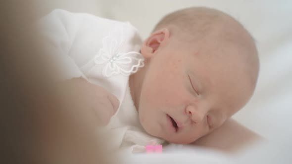 Newborn Baby Girl Asleep While in Her Crib