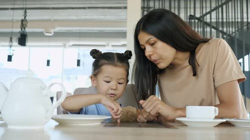 Young Woman Brunette and Toddler Daughter Choose Menu