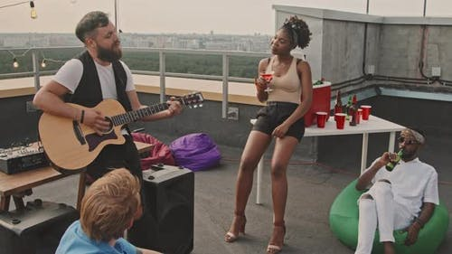 Man Playing Song to Friends on Rooftop Terrace