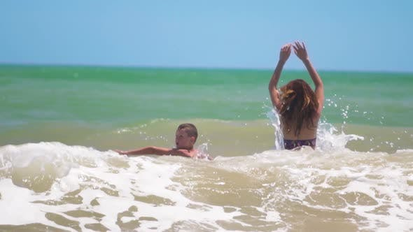 Thumbnail for The Happy Tanned Kid Happily Swimming and Jumping with Mom in Sea Waves on Summer Sunny Day at