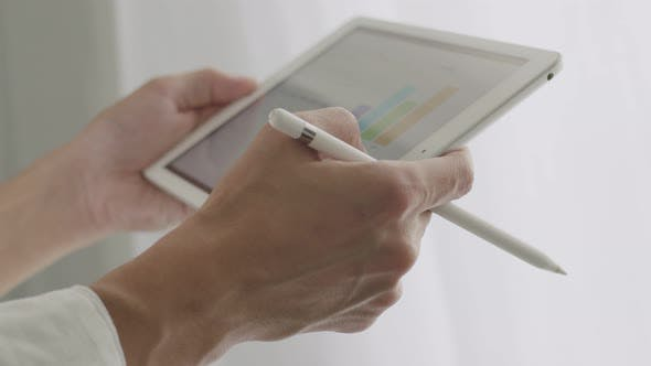 Close-up Asian businessman using tablet examining financial reports.