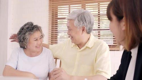 Asia Smart Female Agent bietet Krankenversicherung für ältere Paare nach Dokument