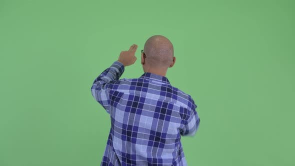 Thumbnail for Rear View of Bald Hipster Man Touching Something