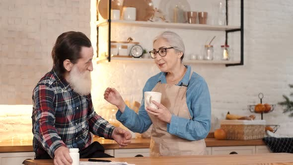 Caring Senior Woman Giving Tea To Senior Man in the Home Kitchen