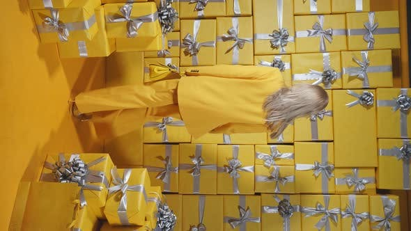 An Attractive Blonde in a Yellow Suit and a Yellow Purse in Her Hands Poses Against the Background
