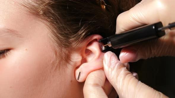Pretty Teenaged Girl Having Her Ears Pierced