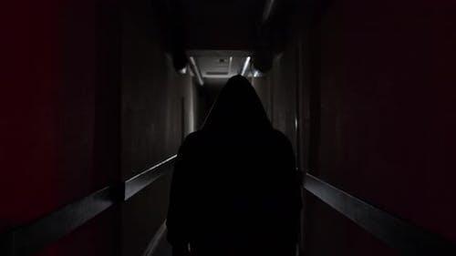 Ein Boxer in einer Motorhaube geht entlang eines dunklen Korridors zu einem Kampf in Zeitlupe