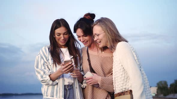 Thumbnail for Group of Female Friends Laughing After Watching Something Funny on Smartphone.