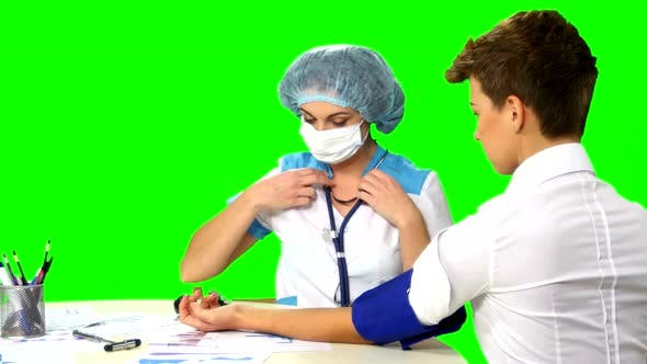 Doctor Taking Blood Pressure of Female Patient on Green Screen