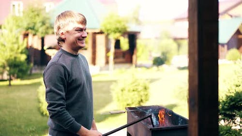 Young Man, Standing Near the Summer House, Prepares the Coals in the Barbecue, for Cooking Pilaf