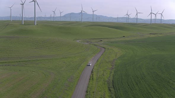 Thumbnail for Car Driving On The Dirt Road Among Windmills