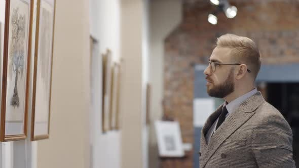 Thumbnail for Thoughtful Man Examining Artwork in Gallery