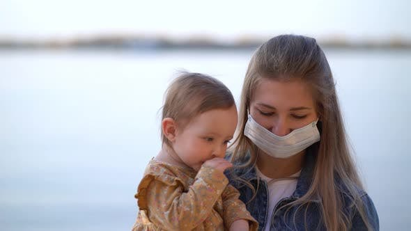 Thumbnail for Masked Mother Holds Hand Lovely Daughter on Beach Walk During Second Wave Quarantine Coronavirus