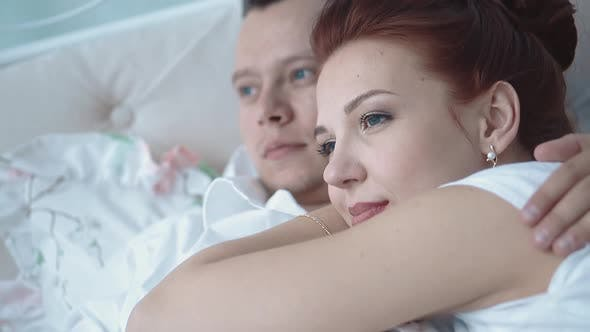 Young Beautiful Couple Resting in Bed Looking Into the Distance Closeup