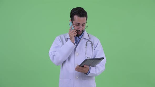 Thumbnail for Happy Young Bearded Persian Man Doctor Talking on the Phone and Using Digital Tablet