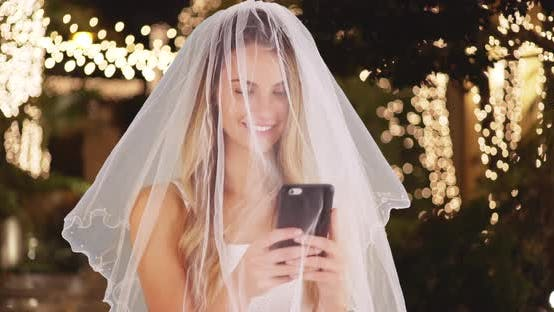 Thumbnail for Closeup of cheerful bride in veil taking selfies outside wedding venue at night