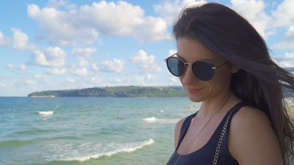 Thumbnail for A Woman Wearing Sunglasses and Smiling Next To Water