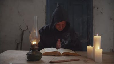 Monk with Bible Reading Prayer in Rustic House