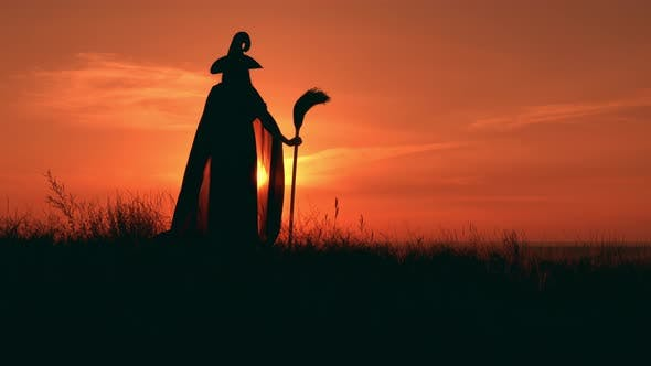 Thumbnail for Girl in Fancy Dress Witch Holds a Besom Looking on Sunrise