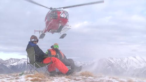 Two men sit on the top of a mountain as a helicopter drops off supplies.