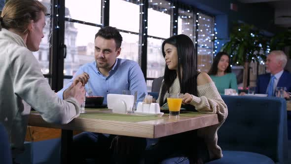 Thumbnail for Group of Friends Talking, Eating in Restaurant