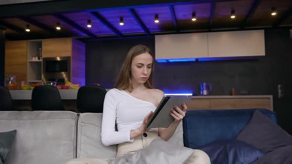 Thumbnail for Woman in Stylish Clothes Sitting on the Sofa at Home and Browsing Apps on i-pad