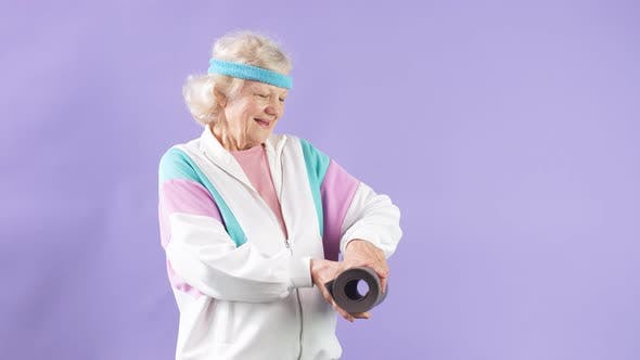 Happy Female Pensioner Holding Yoga Mat in Hands, Comes To Yoga Class in Studio