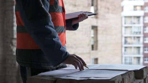 A builder engineer at a construction site works with documentation and drawings.