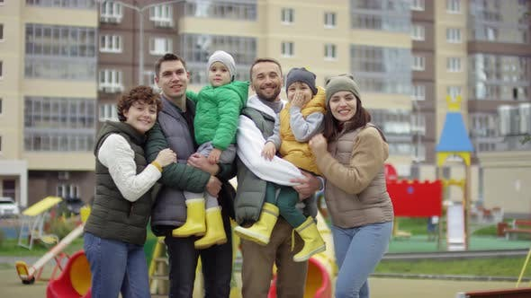 Thumbnail for Happy Neighbor Families Posing Together in Playground of Residential Complex