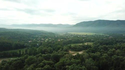 Luftaufnahme des Sonnenuntergangs mit Nebel über Wald und Bergen. Morgen Nebel Rauch im magischen Strahlen Licht