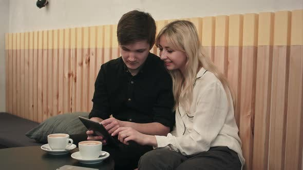 Thumbnail for Young Couple in a Cafe, Drinking Coffee and Using Digital Tablet
