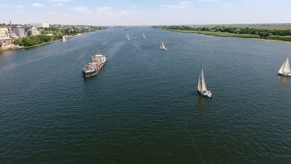 Thumbnail for Aerial Shot of Several Yachts and a Big Barge Floating in the Dnipro in Summer