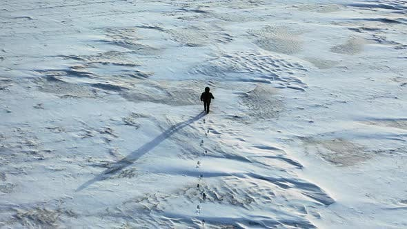 Thumbnail for Aerial View of a Man with a Backpack Walking By the Tundra