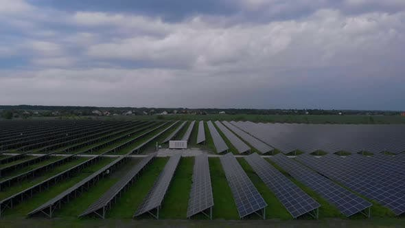 Thumbnail for Aerial Drone View Into Large Solar Panels at a Solar Farm at Cloudy Summer Evening. Solar Cell Power
