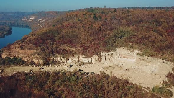 View on the work of equipment in the sand quarry on the background of the forest near the river.