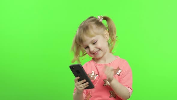 Thumbnail for Kleines Mädchen mit Smartphone. Kind mit Smartphone machen Fotos und Selfies