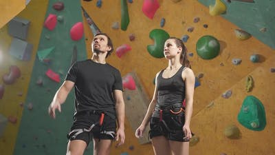 Man and Woman Learning the Art of Rock Climbing at an Indoor Climbing Centre
