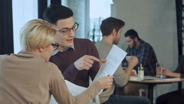 Thumbnail for Business Partners Discussing Documents in a Cafe