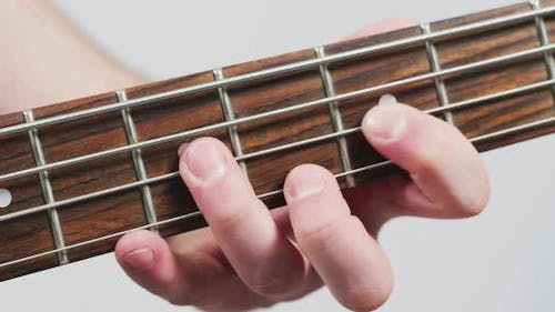 Close up of fingers playing on the fretboard