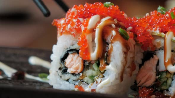 Thumbnail for Close-up of Chopsticks Holds Sushi Roll Over a Plate in Restaraunt. Traditional Japanese Cuisine.